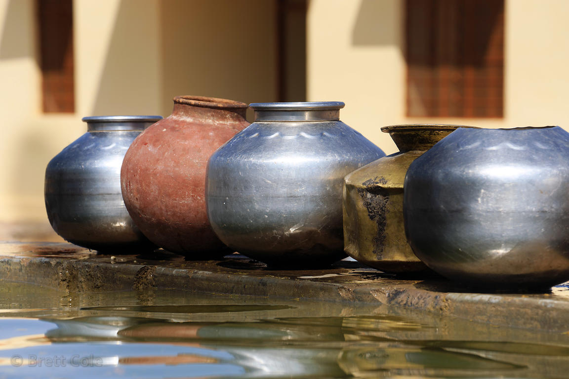 Metal and clay water pots at a water trough, Ganaheda village, Rajasthan, India