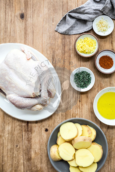 Raw chicken and ingredients on a wooden work surface