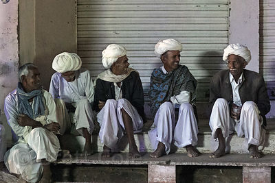 A group of proper Rajasthani men chat before sunrise on a stoop, Pushkar, Rajasthan, India