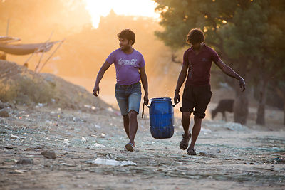 Two men carry a large water vessel, Pushkar, Rajasthan, India