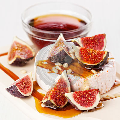 Cheese, figs and honey on light background