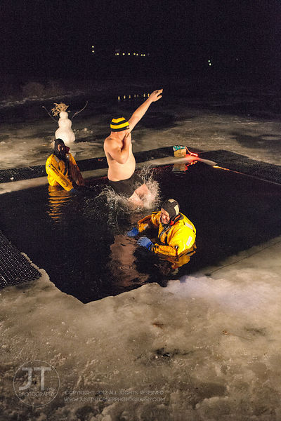 Nick Bedell jumps into the frigid water during the Hawkeye Wrestling Club's Polar Plunge at the Brown Deer Country Club in Co...
