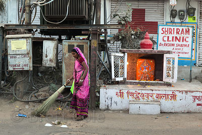 A woman sweeps a street near a small shrine, Pushkar, Rajasthan, India