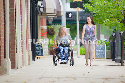 Young woman using a wheelchair on a city sidewalk with her friend