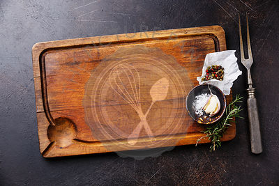 Wooden cutting board background with seasoning, herbs and kitchen fork on dark background copy space