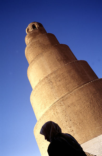 A woman in chador walks past the minaret of the ancient mosque at Samarra