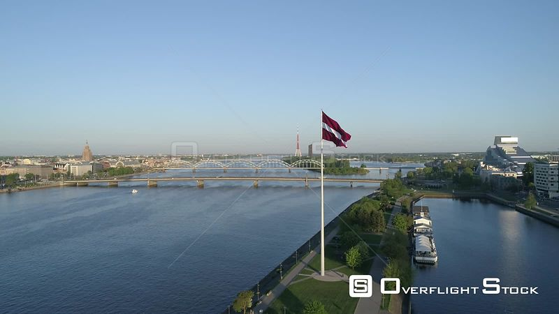 Aerial drone shot approaching a large flag of Latvia with skyline of Riga in background
