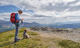 A hiker feeding their dog on the summit of Barrow in the Derwent Fells in the English Lake District.