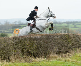 James Mossman jumping a hedge at Wilson's - The Cottesmore Hunt at Manor Farm