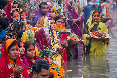 Hindu devotees await sunrise on the Ganges River during Chhath Puja, Varanasi, India. Chhath Puja is a devotion to the Sun Go...