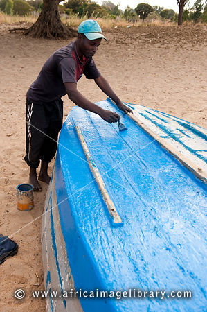 man painting his boat on the beach of Lake Malawi, Nkhotakota, Malawi
