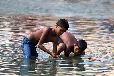 Boys search for money in the Ganges River, Haridwar, India