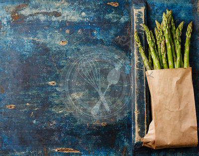Fresh raw Green asparagus in paper bag on blue wooden background copy space