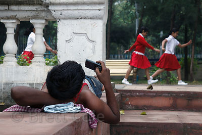 A man checks his mobile phone as a school group passes, Princep Ghat, Kolkata, India.
