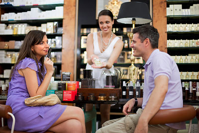 Croatia, Zagreb, Saleswoman showing perfume bottle to couple