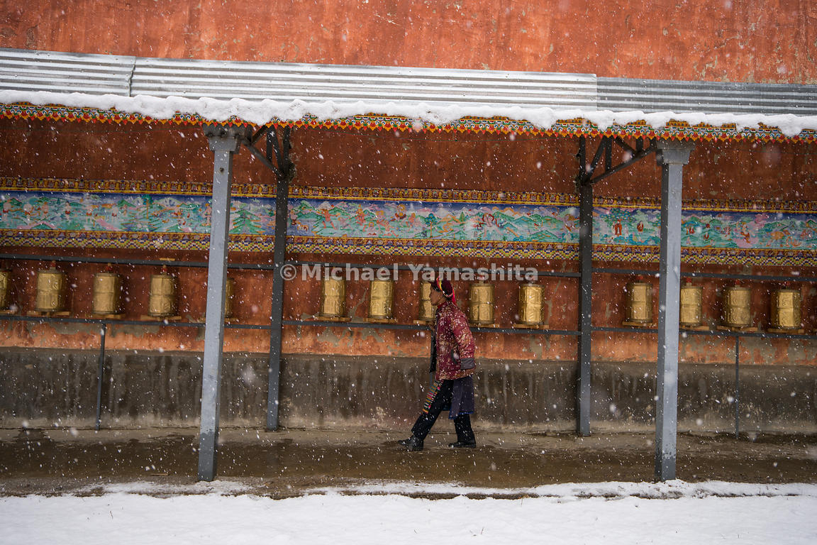 A villager walks past bronze prayer wheels lining a wall of the Fei Lai Shi temple, a Buddhist shrine in Yunnan's snowy backc...