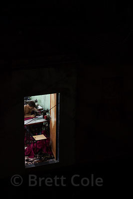 View into a window at night, showing a garment factory,  Dharavi slum, Mumbai, India.