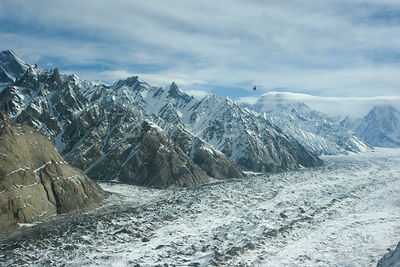 Aerial view of a glaciated valley, Concordia in the Karakoram Mountains, with helicopter in distance. Himalayas, Pakistan. Fr...