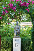 Statue of a terracotta warrior from Xi'an crouching on a pedestal marked with the word 'China', framed by pink flowered rose....