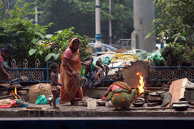 Family tends a fire while living on a median strip, Taltala, Kolkata, India