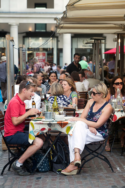 UK - London - A man and a woman talk at an outside table at a restaurant in Covent Garden Market