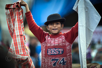 A boy sells clothes at a market in Kullu, India