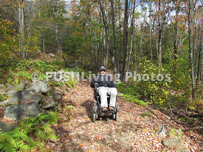 Man in a power wheelchair enjoying a forest trail