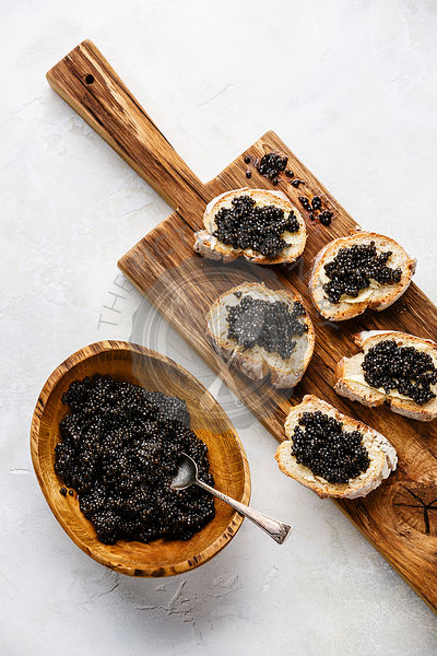 Sturgeon black caviar in wooden bowl and sandwiches on white background