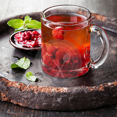 Hot tea with raspberry on dark background
