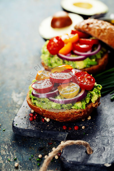 Tasty homemade sandwiches with avocado, tomato, onion and pepper on a slate board