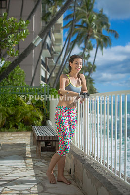 Young woman with a prosthetic arm exercising in a tropical setting overlooking the ocean