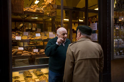 Italy - Bologna - Two men in discussion on a street in the Mercato di Mezzo