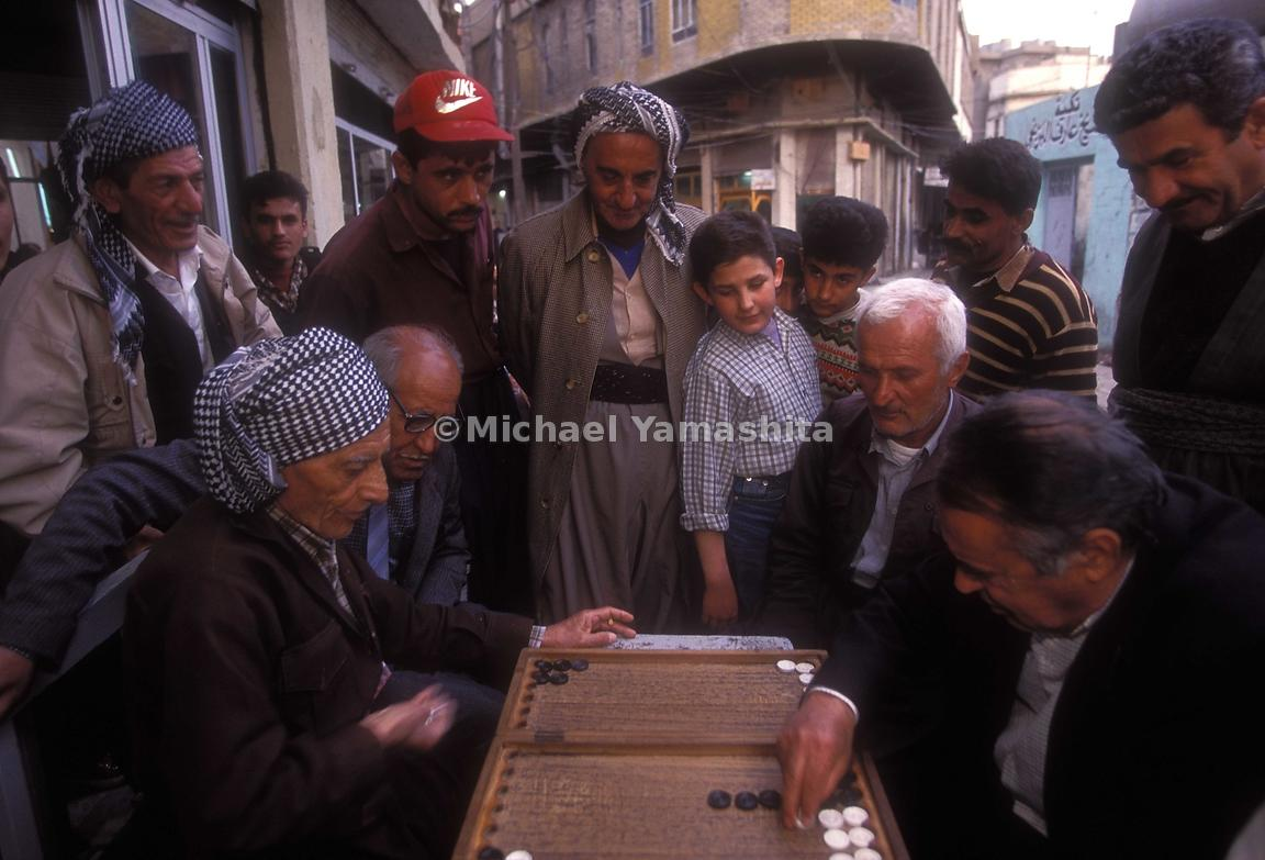 Spectators observe a game of Backgammon in Iraq.