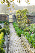 Brick paths in the walled kitchen garden pass beds edged with step-over apples and clipped box towards a gate leading into su...