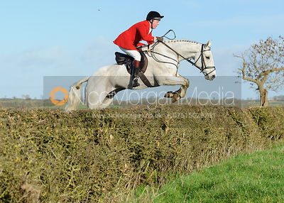Tom Kingston jumping a hedge at Mrs Greenall's covert