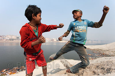 Two boys playfight in white sand dunes along the Ganges River, Varanasi, India.