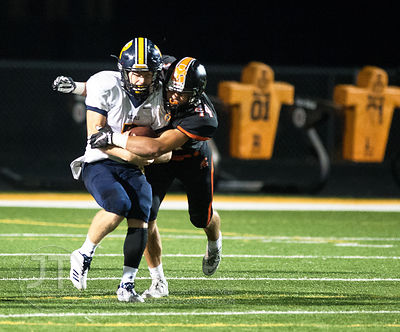 Solon's Ryan Geistkemper (44) lays a hit on  Iowa City Regina's Michael Conlon (2) during the second half of play in Solon on...