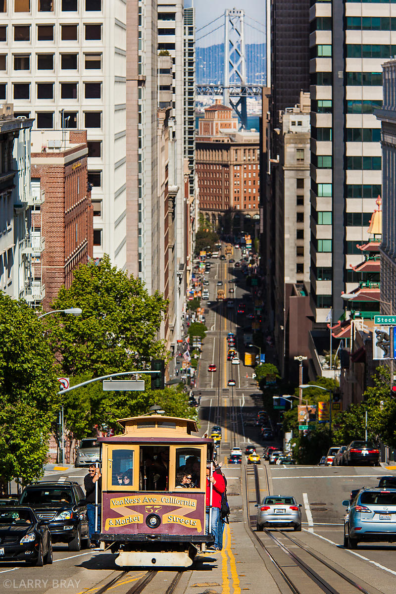 Cable car viewed down Powell Street with Bay Bridge in the distance in San Francisco, California, USA