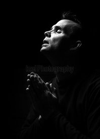 High contrast black and white image of a man praying