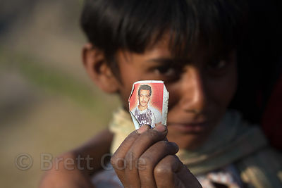 A boy holds up a small photo of a relative, Ajaysar, Rajasthan, India