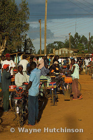 Street seen in Kenya Africa with people on bicycles along side of dusty road , Mumias , Kenya