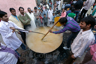 Men stir a huge wok during the Muharram festival, Jodhpur, Rajasthan, India