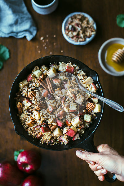 A woman is holding a cast iron skillet filled with warm breakfast farro bowl.