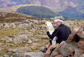 LAKE DISTRICT, CUMBRIA, ENGLAND, UK - SEPTEMBER 02, 2017: A female hiker reading a map on the summit of Great Borne in the Gale Fells in the English Lake District