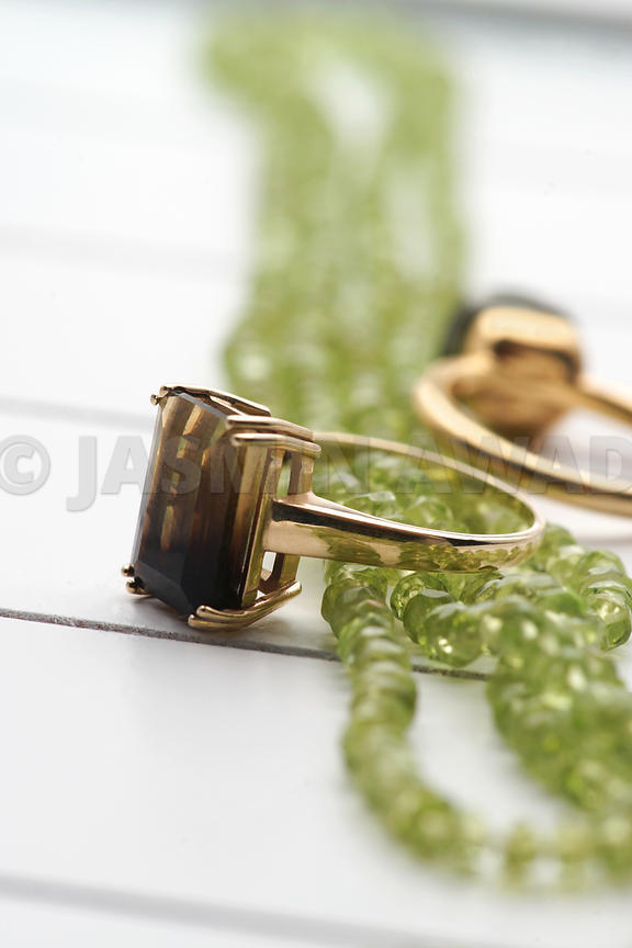 Mixed jewelry -green peridot necklace and gold rings with smokey quarz..Studio Shot Shallow DOF