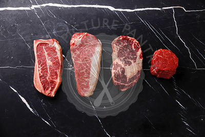 Variety of Raw Black Angus Prime meat steaks Blade on bone, Striploin, Rib eye, Tenderloin fillet mignon on dark marble backg...