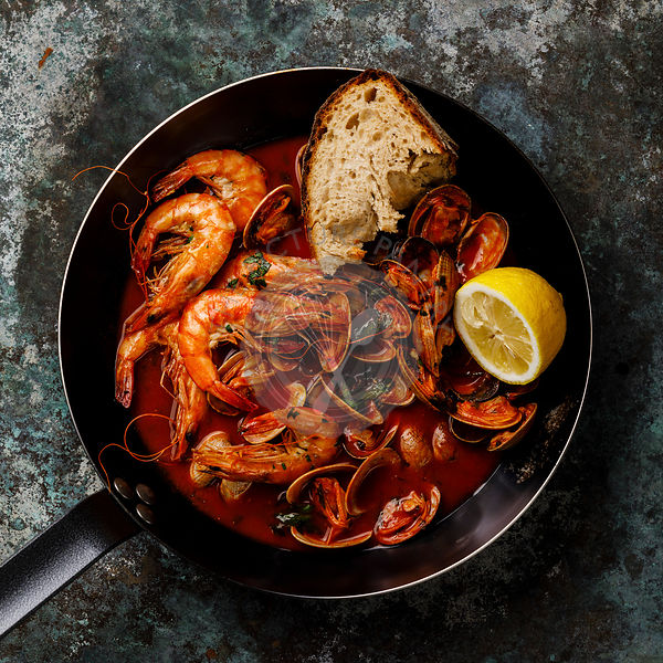 Cooked Vongole Clams and pink Prawn Shrimp with tomato sauce and parsley in cooking pan