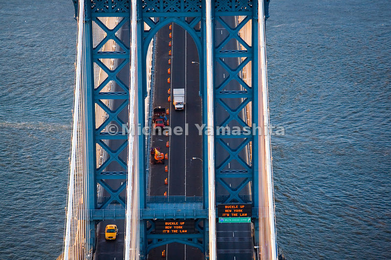 The Manhattan Bridge carries seven lanes of roadways and four subway tracks, as well as pedestrians and cyclists.  New York C...