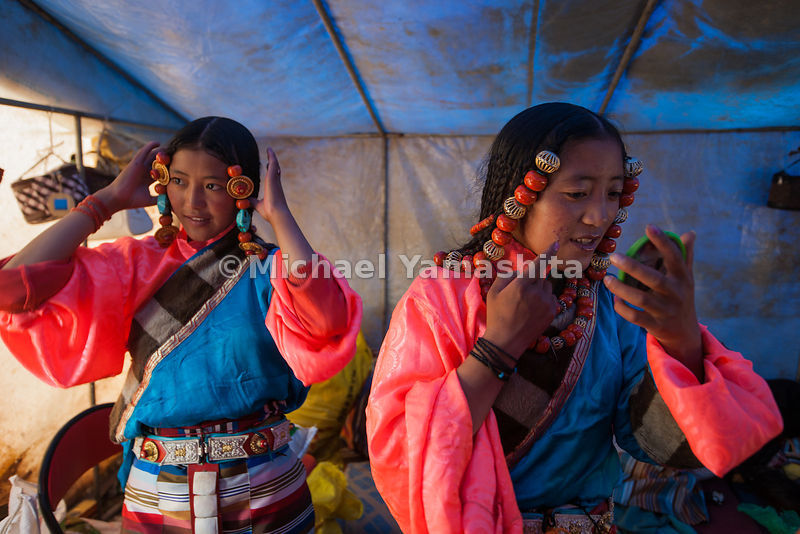 Young women in typically colorful Tibetan costumes primp before their upcoming traditional dance performance at the festival.