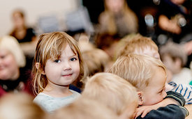 Little Nordic girl sitting in a crowd of children